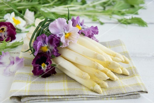 A bunch of white asparagus tied with pansies