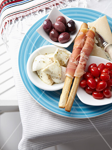 A plate of starters with olives, cheese, mozzarella, tomatoes and grissini