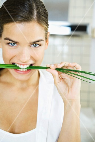 Woman biting into chives, smiling