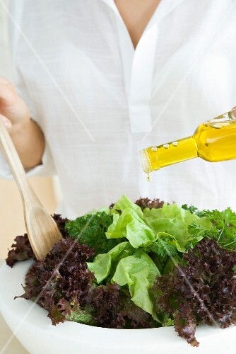 Woman preparing salad, pouring olive oil dressing