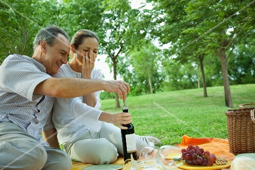 Mature couple having picnic outdoors, opening bottle of wine