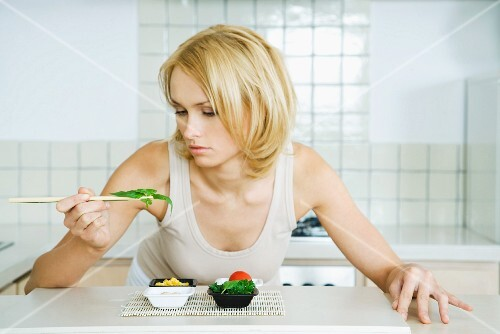 Young woman leaning over kitchen counter, picking up herbs with chopsticks