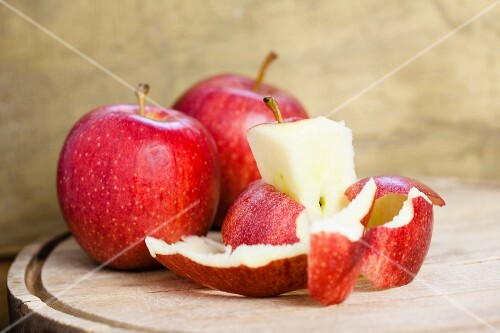 Red apples and leftovers of apples on a chopping board