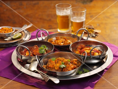Four different types of curries on a tray