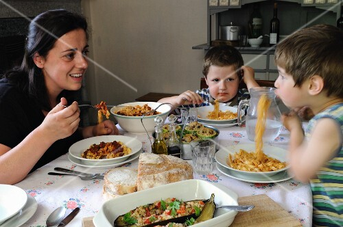 A mother and two children sitting at a table eating tagliatelle
