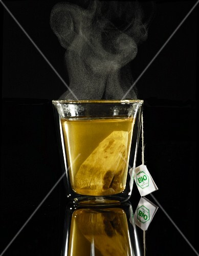 A glass of steaming tea with a teabag