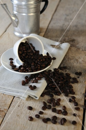 Coffee beans falling out of an espresso cup