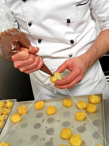 Profiteroles being filled with nougat cream