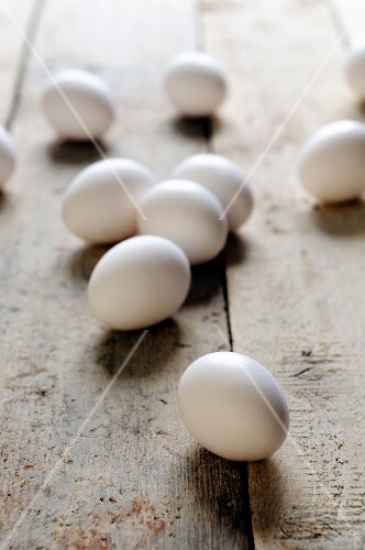 White eggs on a wooden surface