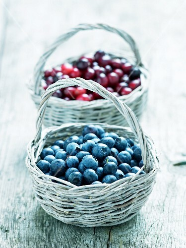 Blueberries and cranberries in baskets