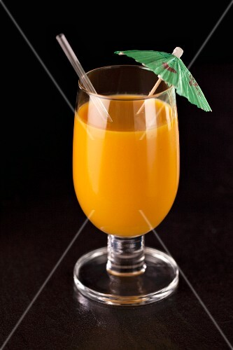 An orange smoothie with a cocktail umbrella