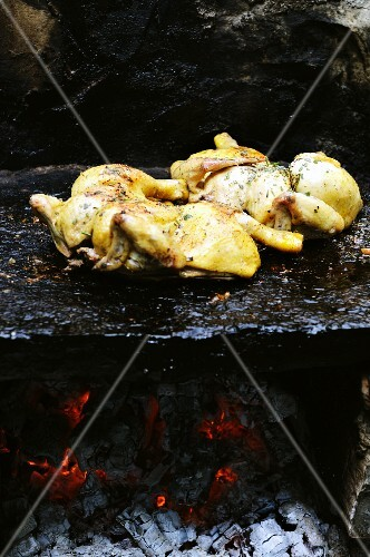 Spatch-cock chickens cooking on a granite stone over fire