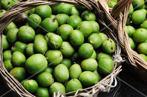 Freshly picked green walnuts in baskets