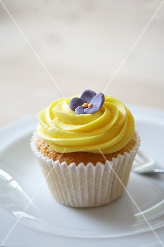 A lemon cupcake decorated with a sugar flower
