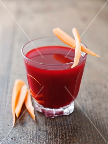 A glass of beetroot juice with carrots
