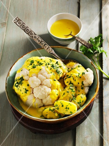Cauliflower with a saffron and cheese sauce and boiled potatoes