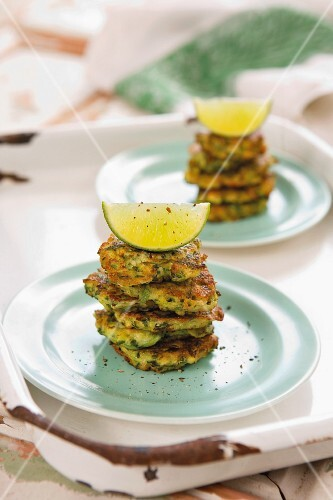 Stacked courgette fritters with lime wedges