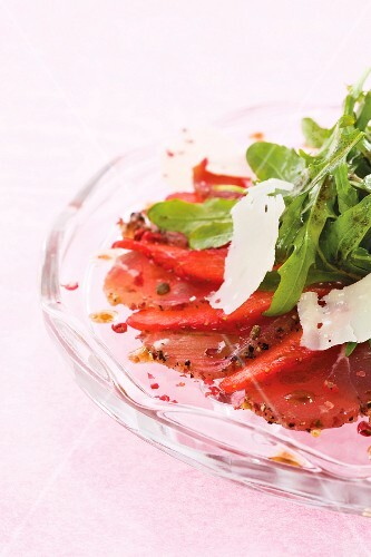 Beef and strawberry carpaccio with pink peppercorns, rocket and parmesan