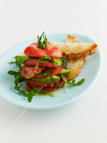 Tomato and avocado tower with bacon and toast