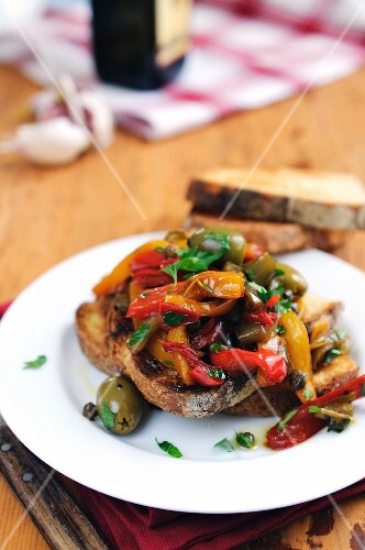 Bruschetta topped with red and yellow peppers, olives and capers