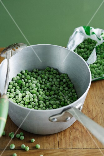 Pot of frozen peas on wooden table