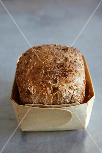 A loaf of wholemeal bread in a wooden basket