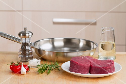An arrangement of raw fillet steaks, herbs, spices, a pan and oil