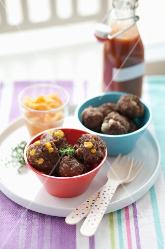 Two Small Bowls of Assorted Meatballs on a Tray with Plastic Forks