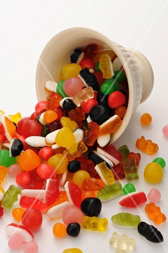 Various sweets falling out of a cup