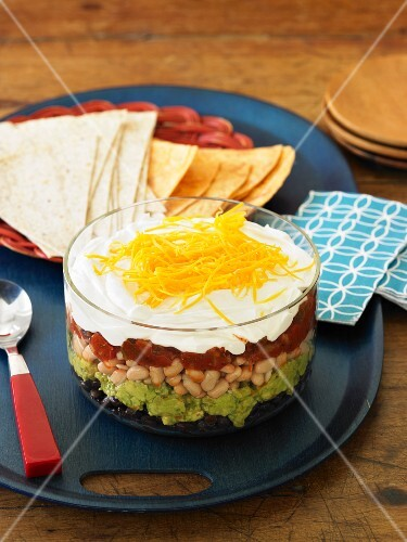 Six Layer Mexican Dip with Black Beans, Cannellini Beans, Guacamole, Salsa, Sour Cream and Shredded Cheddar Cheese