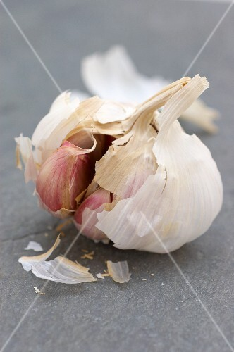 An opened garlic bulb on a slate surface