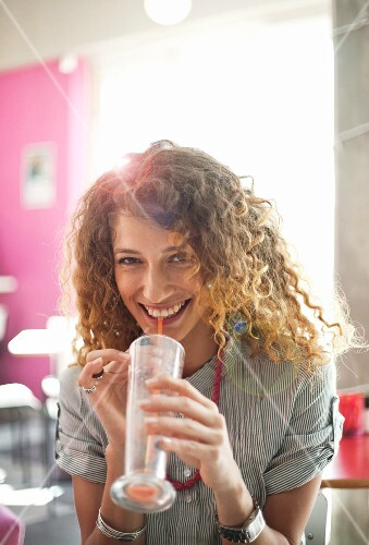 Smiling woman drinking in cafe