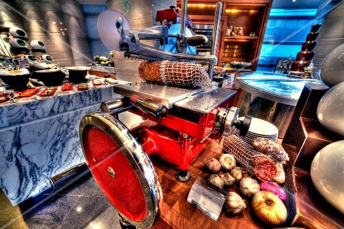 A cutting machine with salami and ham on a buffet