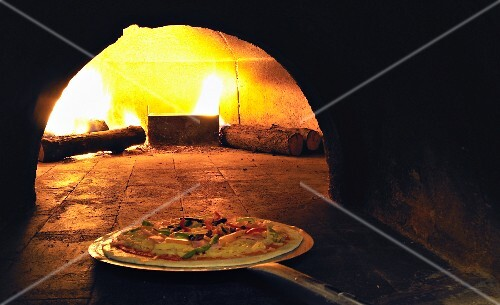 A pizza being placed in a wood-fired oven
