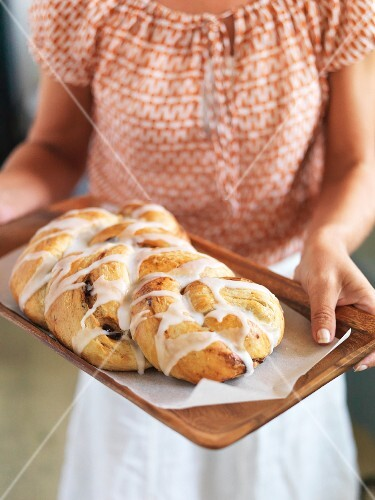 A woman serving a tray of cinnamon and date bread