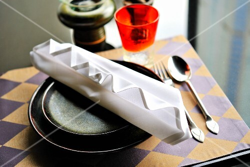 A place setting with an artistically folded napkin