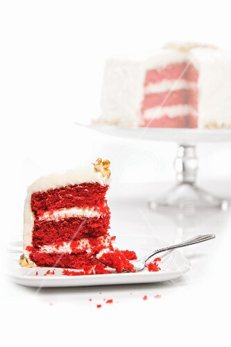 Slice of Red Velvet Cake On a Plate with Whole Cake in Background