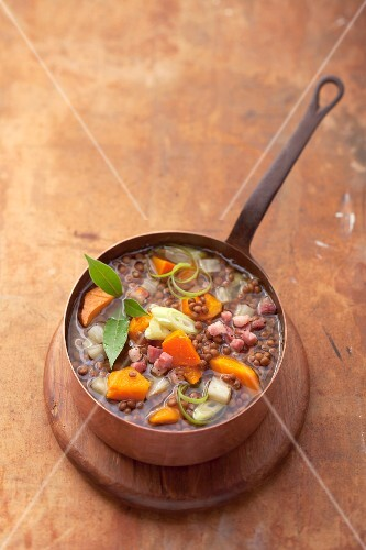 Lentil soup with diced bacon in a copper pan