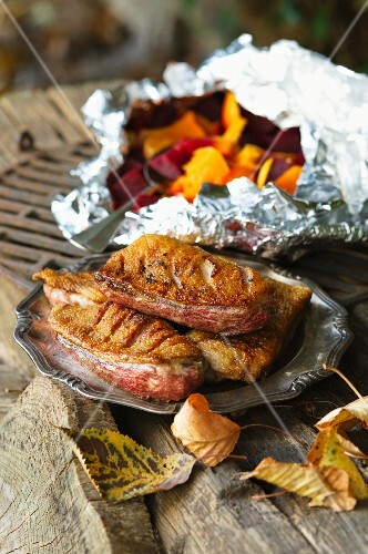A duck on a barbecue with vegetables