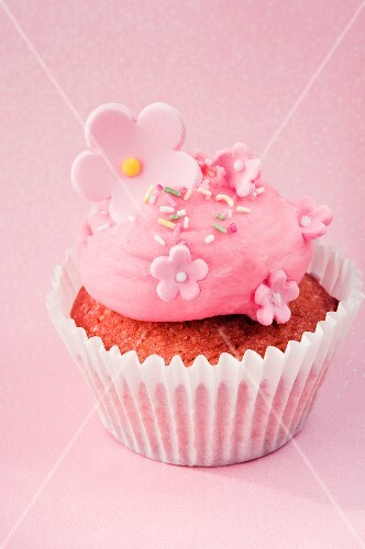 A cupcake decorated with pink cream and sugar flowers