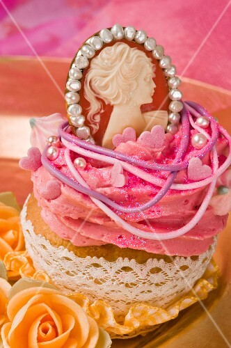A cupcake decorated with buttercream and a Marie Antoinette pendant
