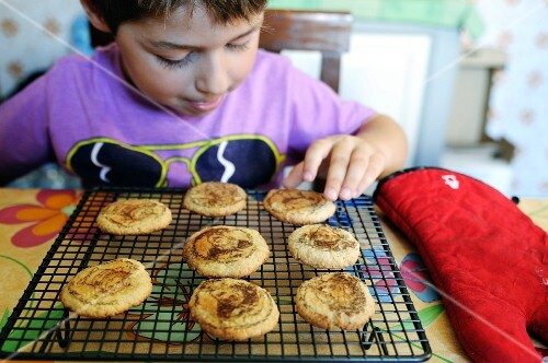 Young boy choosing a cookie from the baking rack