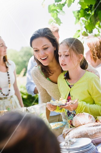 A mother and daughter standing by the buffet at a garden party