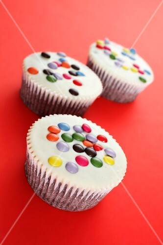 White cupcakes decorated with coloured chocolate beans