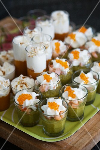 Various types of vegetable puree in glasses topped with whipped cream