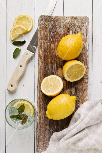 Lemons on a wooden board and a glass of lemon water