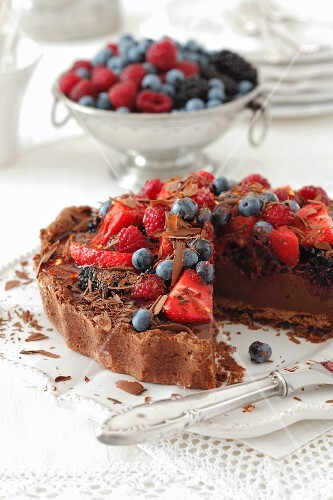 A chocolate cake topped with berries, sliced