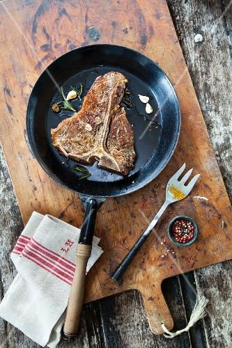 T-bone steak in a pan (seen from above)