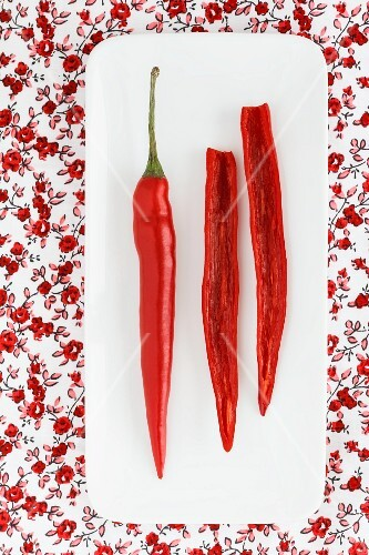 A whole and a halved chilli pepper on a plate (seen from above)