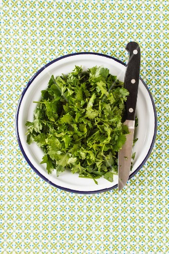 Freshly chopped coriander on a plate with a knife